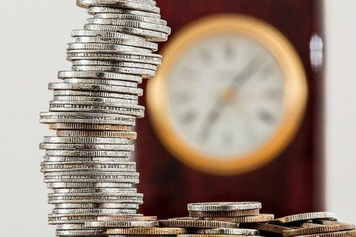 コインが積み重なって時計の前にある画像