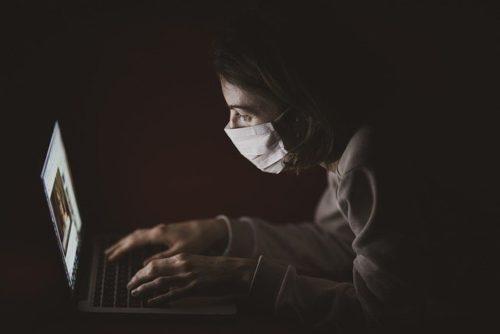 暗闇でマスクをしてパソコンをいじる女性