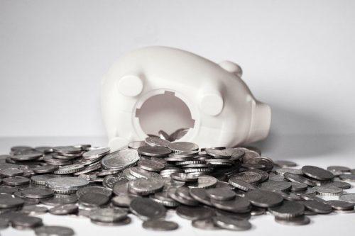 豚の貯金箱が割れて小銭があふれ出している画像