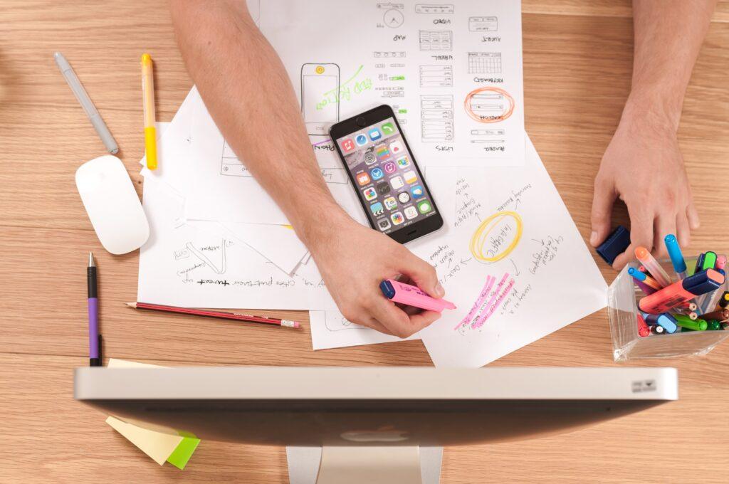 机の上で勉強をしており、紙が散らばりiPhoneが置いてある画像