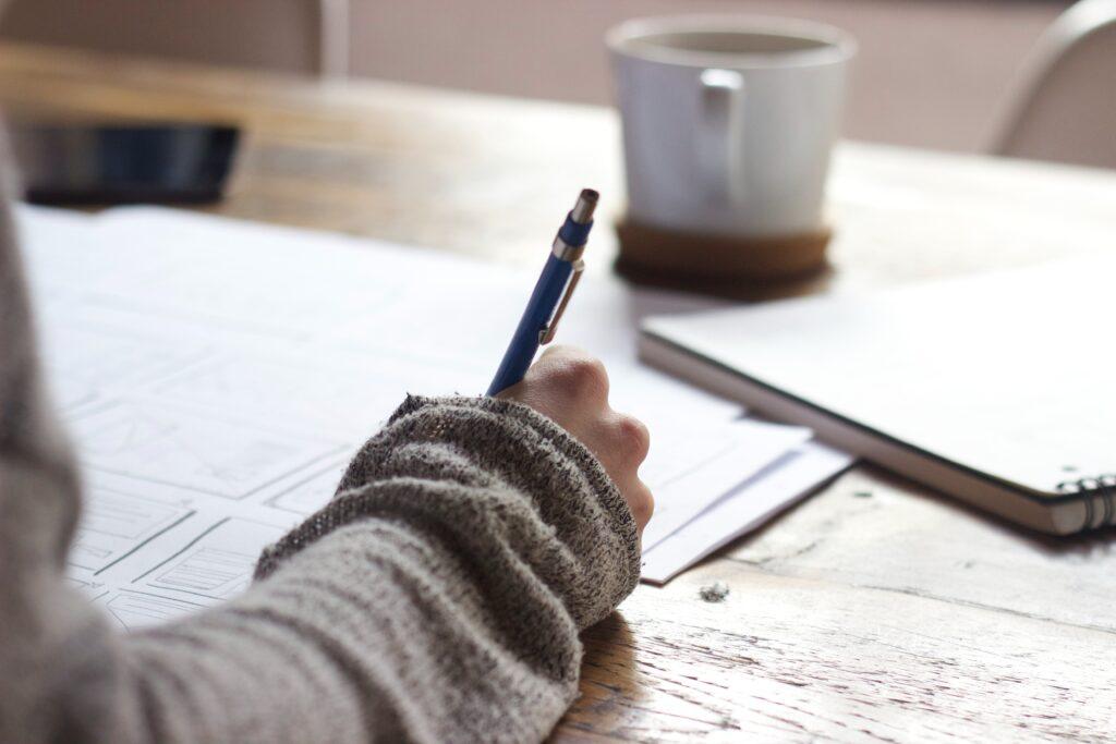 机にコーヒーを置いて勉強している
